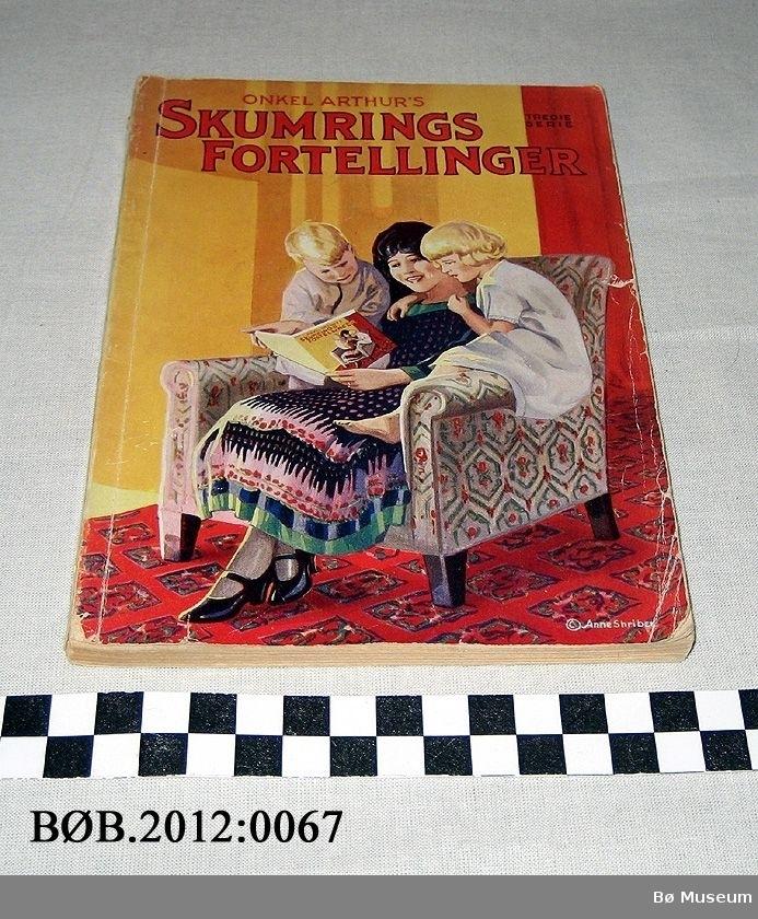 Kvinne i stol, leser for to barn.