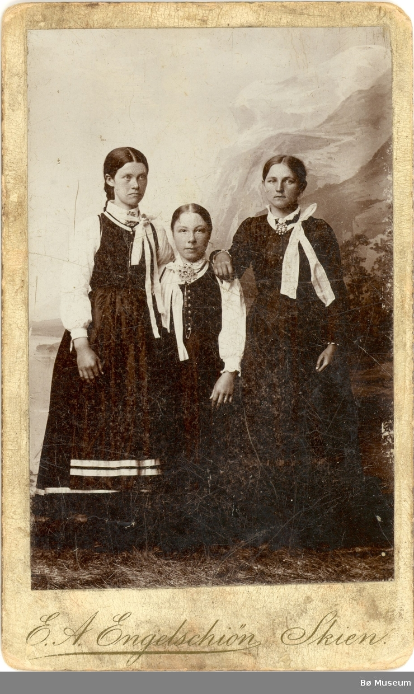 Tre yngre kvinner i vesttelemark-drakt i fotoatelier. Kvinna t.h. er Liv O. Nørsthaug, gift Tjønntveit i Øvre Bø. Dei andre er to venninner.