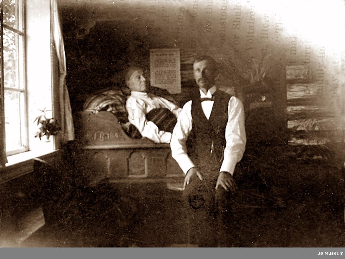 Eldre mann ligg i kroneseng og yngre mann sit framfor