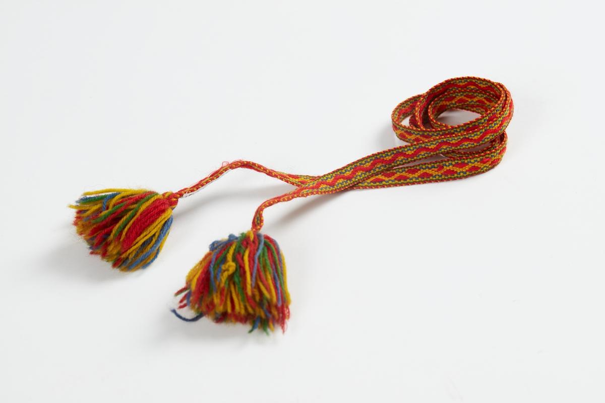 Vevet bånd av ullgarn, siksakmønster i rødt og gult, med flerfargete dusker av ullgarn. Bruk usikker, muligens til drakt, komse eller annet.