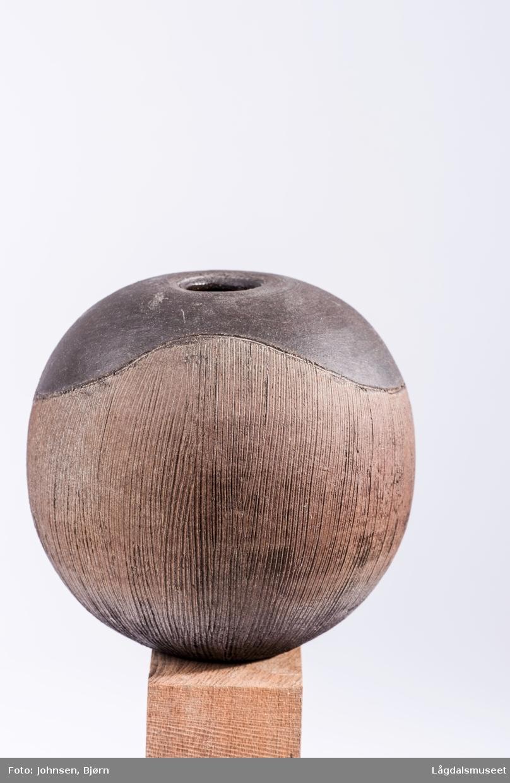 En markert timeglassform i en mørkere nyanse på toppen av vasen er eneste motiv.