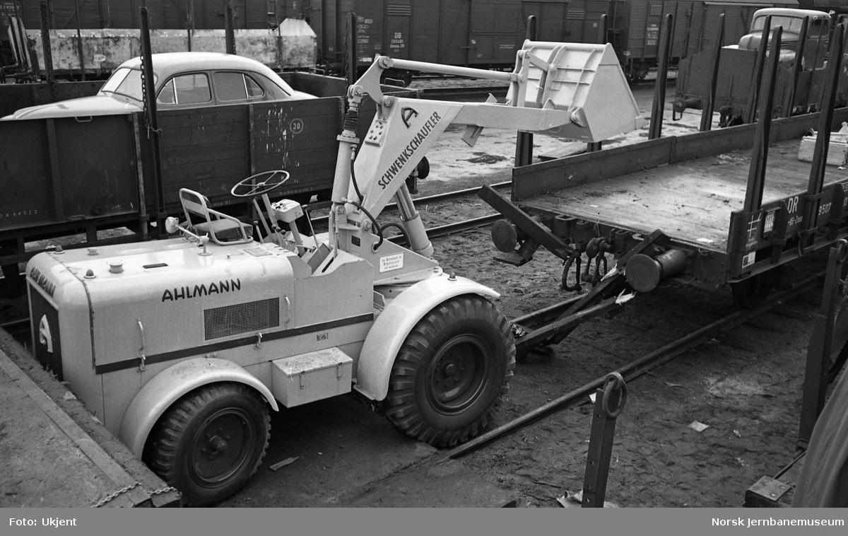 Last på åpen godsvogn, transportskader. Ahlmann schwenkschaufler som har falt ned. Ny personbil på tsjekkoslovakisk godsvogn i bakgrunnen
