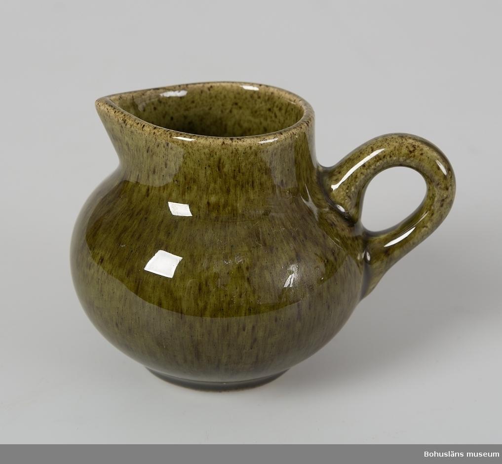 Gräddkanna av keramik glaserad i mörkt gröngult melerat med brunt inslag. Rundad (bollformad) kropp, nästan rak kant ca 1 cm upptill. Liten pip bildas genom att mynningskanten är V-formad och utböjd till en liten spets på ett ställe. På motsatta sidan längre ner finns ett öra vars böj är riktad snett uppåt. Mycket otydlig stämpel på undersidan. Klisterrest efter etikett? på ett ställe. Hör samman med kaffekopp UM26835, assiett UM26836 och sockerskål UM26838. För ytterligare uppgifter se UM26835.