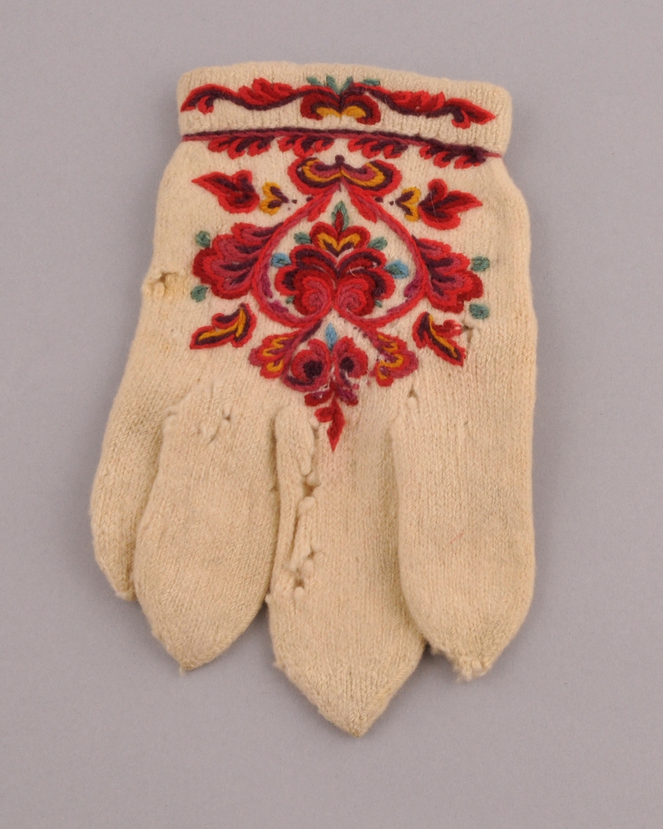 Fingervott (til høgre hand) strikka av kvitt/ubleika totråds ullgarn. Fleirfarga rosesaum på handbaken (sauma med laust tvinna totråds ullgarn) omkring handleddet og på tommelen.