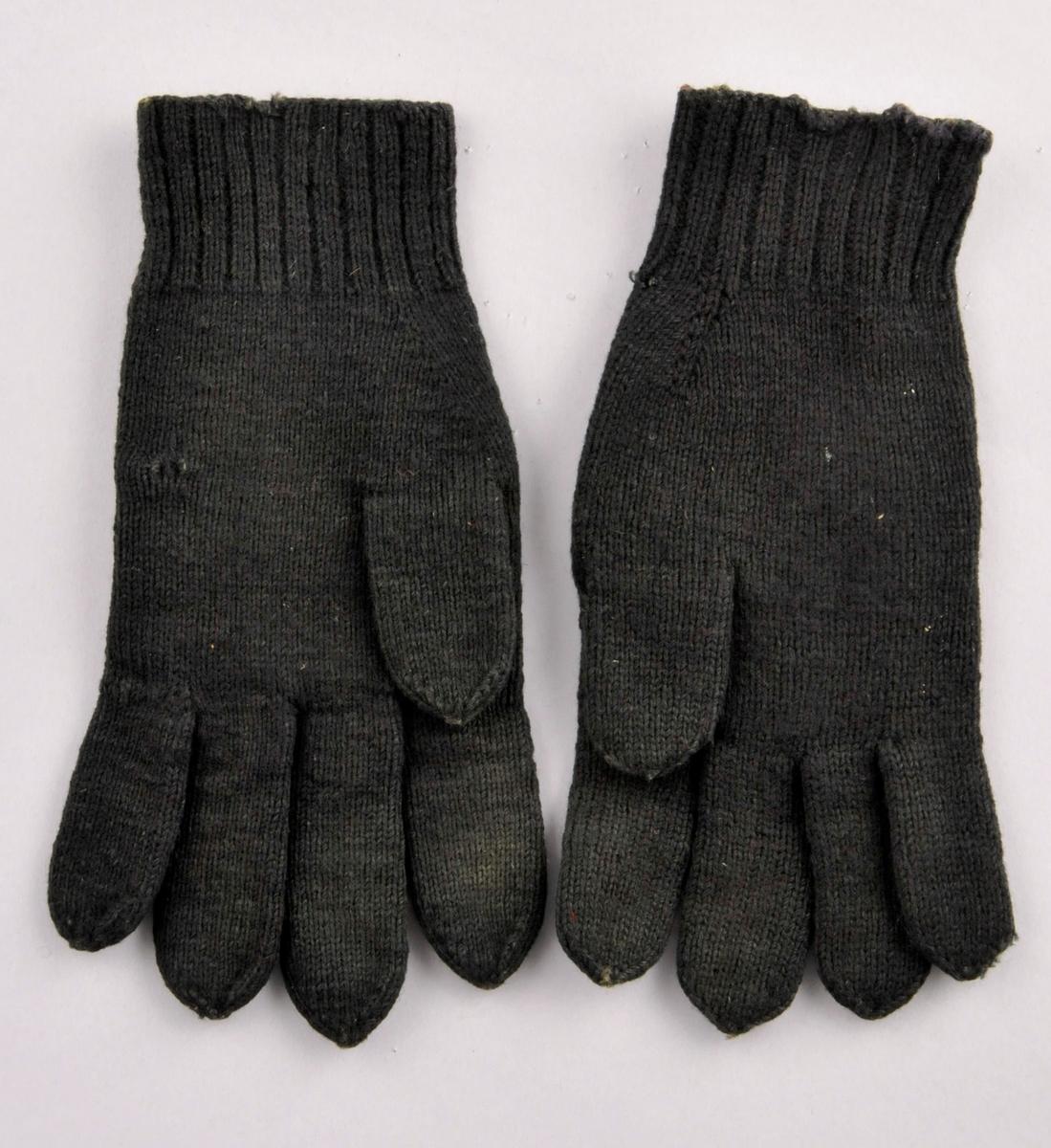 Svarte glattstrikka fingervottar med fleirfarga ullgarnsbroderi med blomstermotiv i sjattersaum på handbaken. Votten har 5 cm vrangbord av to rette og to vrange masker.