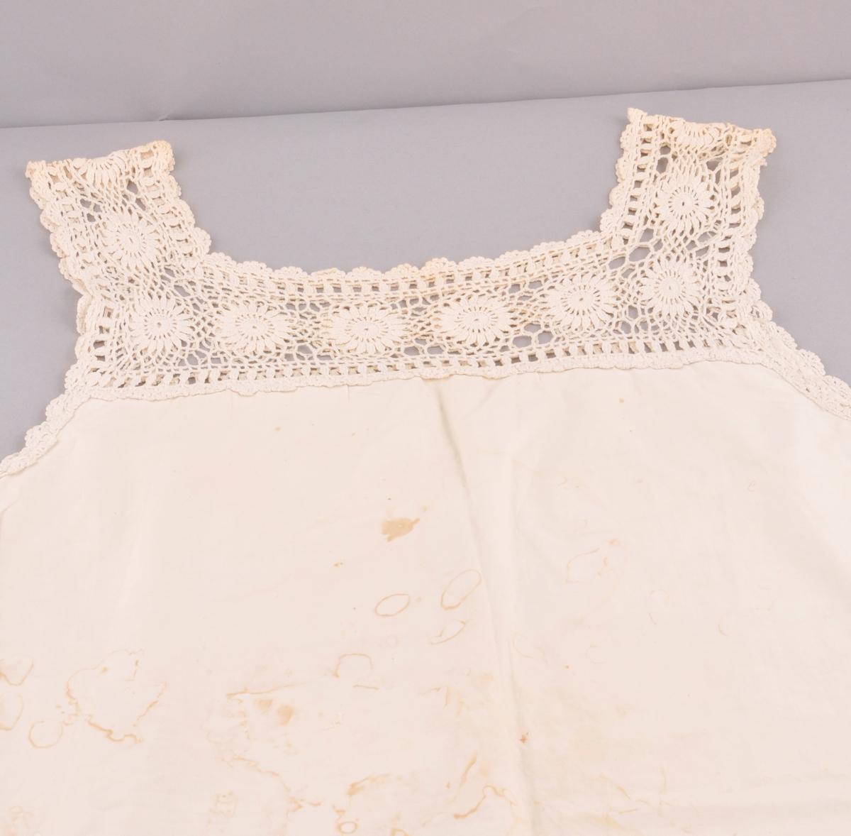 Kvitt bomullslerret, forma som kjole, armlaus, kanta med kvit hekla blonde langs armhol.Hekla berestykke og selar. Ein trekanta kile, sett saman av to stykker i kvar side nede. Klaff med stofftrekkte messingknappar nederst. (Dannar hol til beina). Maskinsydd.