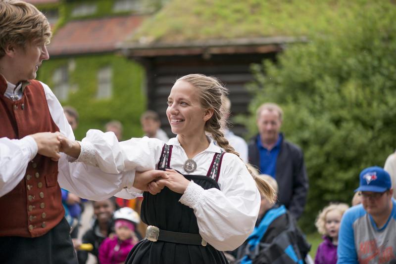 Mann og kvinne i folkedrakt danser folkedans.