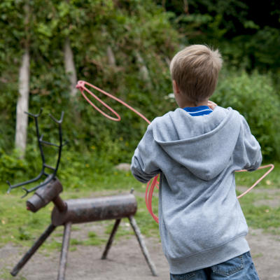 Boy using lasso on a manmade iron reindeer