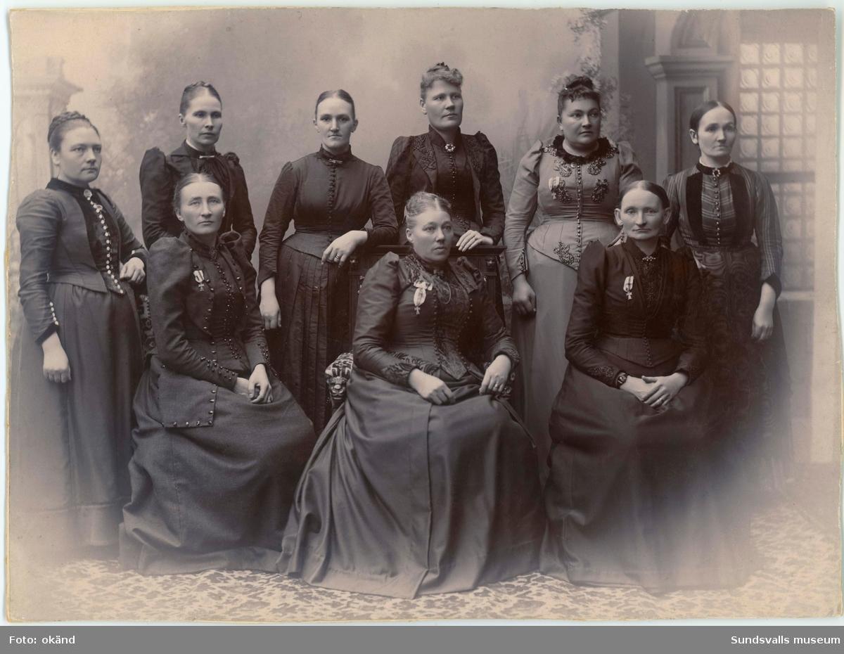 Sundsvalls Barnmorskesällskap, bildat 1887. Initiativtagarna var stadsbarnmorskan Amalia Henriksson (sittande längst ut till höger) och stadsbarnmorskan Anna Hydén (sittande längst till vänster). Amalia var ordförande i sällskapet under 34 år och Anna var sekreterare i 45 år. Bägge fick patriotiska sällskapets medalj efter lång och trogen tjänst. Kvinnan som sitter i mitten är okänd (ev kassör). Kvinnan som står fjärde från vänster heter Augusta Heitz (1855-1925) och var barnmorska i Skönsberg.