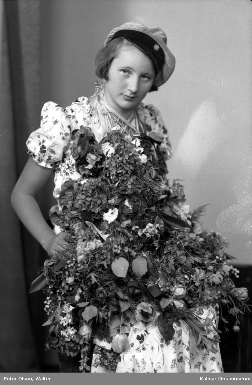Ateljébild på en kvinna som har tagit realexamen. Enligt Walter Olsons journal är bilden beställd av Aina Pettersson ifrån Ölandsgatan 11.