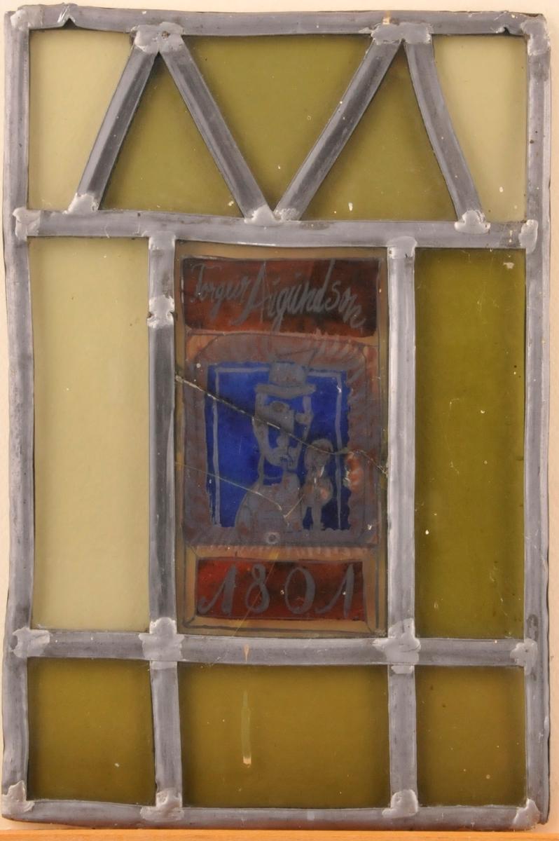 Blyinnfatta glas, midtfeltet i blått og raudt med påskrift og teikning.