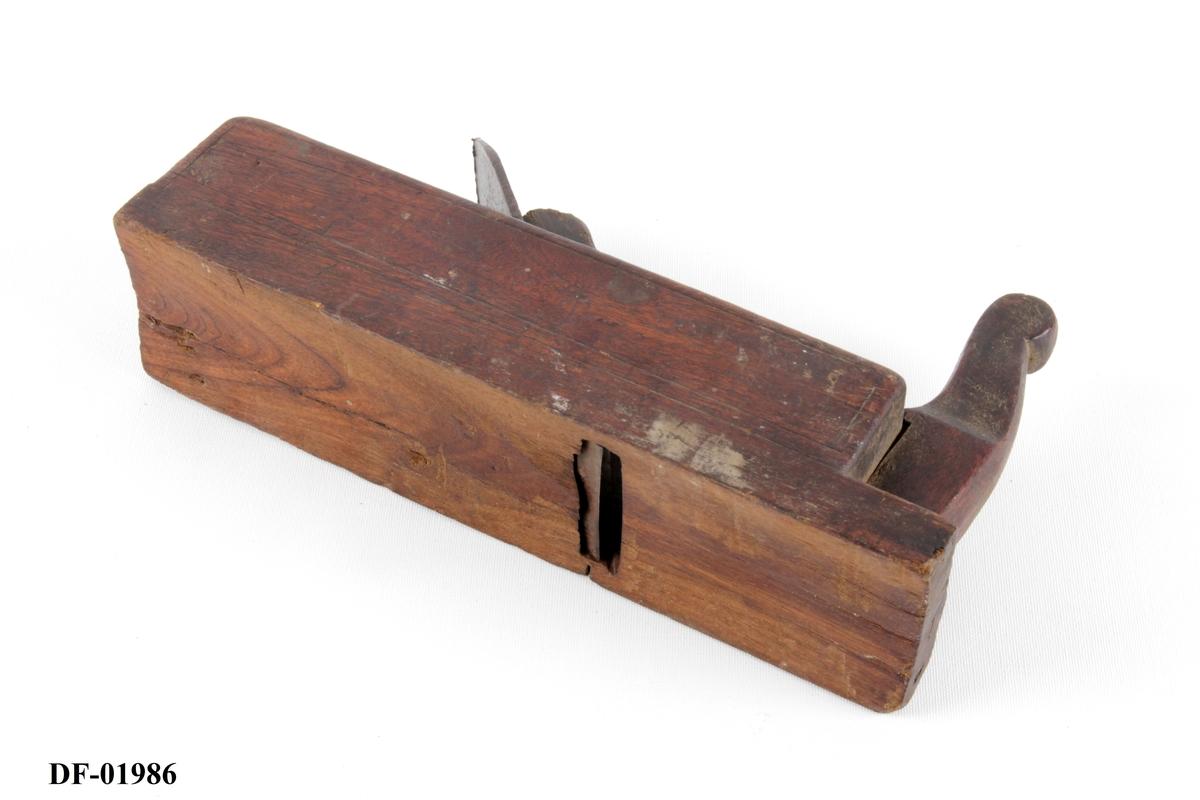 Rektangulær stokk med jern, kile og horn. Svakt buet såle. Innfelt horn. Vinkel på høveljern er 44 grader.