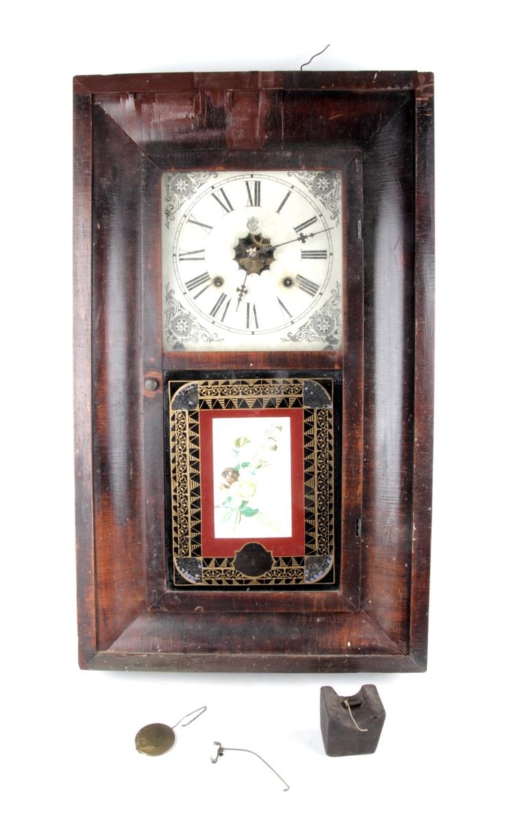 Vitrinen er dekorert med et floralt motiv omkranset av en gullbord.