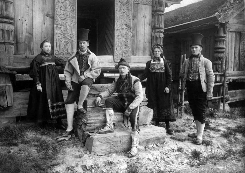 Kvinner og menn i drakter foran loftet fra Rofshus