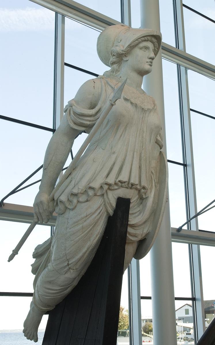Galjonsbild tillhörande fregatten Minerva och senare fregatten Göteborg. Hjälmprydd kvinnofigur bärande spjut i den längs kroppen hängande högra armen och sköld i vänstra armen. Den rikt draperade dräktern är tvådelad. Överdelen är hopfästad synlig fjällmönstrad brynja.