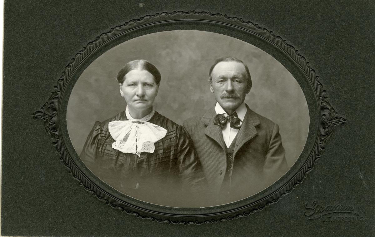 Portrett av en eldre kvinne og mann. Kvinnen er iført en kjole med stor krage mens mannen er iført dress med sløyfe i halsen.