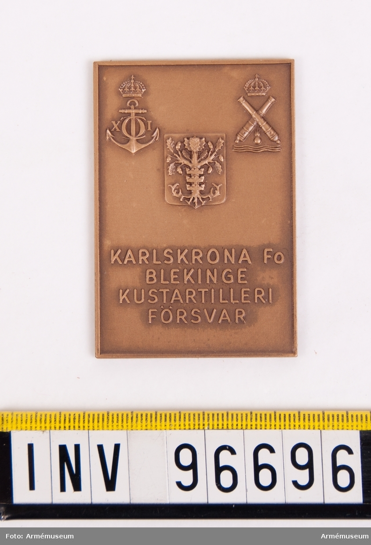 Plakett i brons för Karlskrona försvarsområde Bleking kustartilleriförsvar. Plakett upptagande Blekinge vapen på sköld samt Karlskrona stads vapen och kustartilleriemblemet jämta inskrift KARLSKRONA FO BLEKINGE KUSTARTILLERIFÖRSVAR, det hela omgivet av upphöjd kant. Stans nr 4354. Stans härdad 1961-01-05.