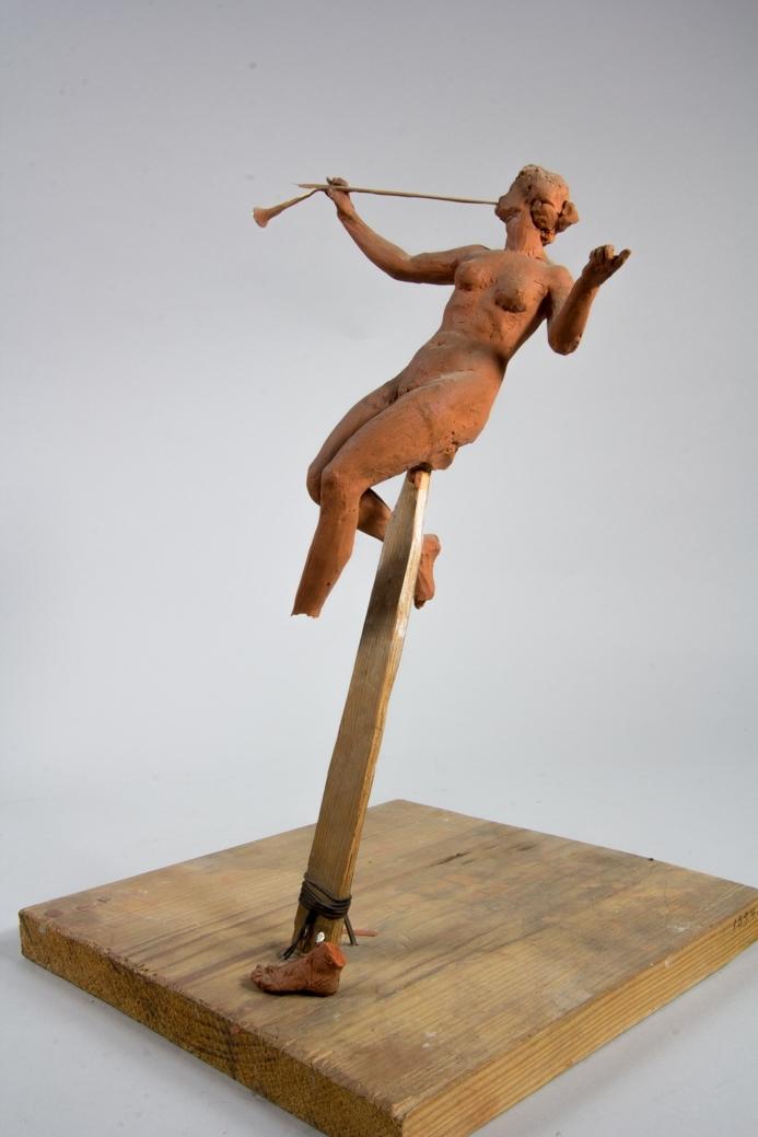 Naken kvinna i helfigur, Fama, med utbredda armar. Hon håller en trumpet.