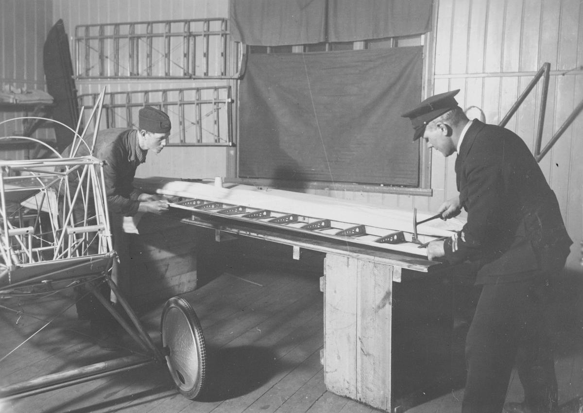 Flygplansbygge. Tyghantverkare George Holmberg och okänd miltiär i arbete med att klä en flygplansvinge med duk på flygplanet Holmberg Racer.
