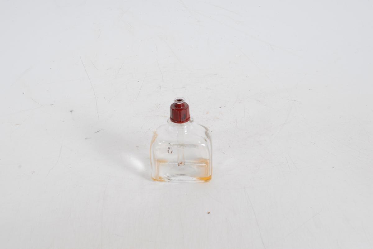 Form: Firkantet med avrundet topp og skrukork som har et glassrør festet til seg (som går ned i flasken).