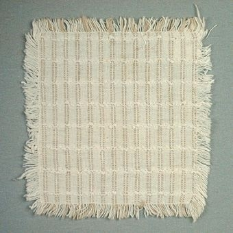 Randig servett i vitt och beige med en grövre vit tråd som bildar ett rutmönster.1.5 cm frans runt om.