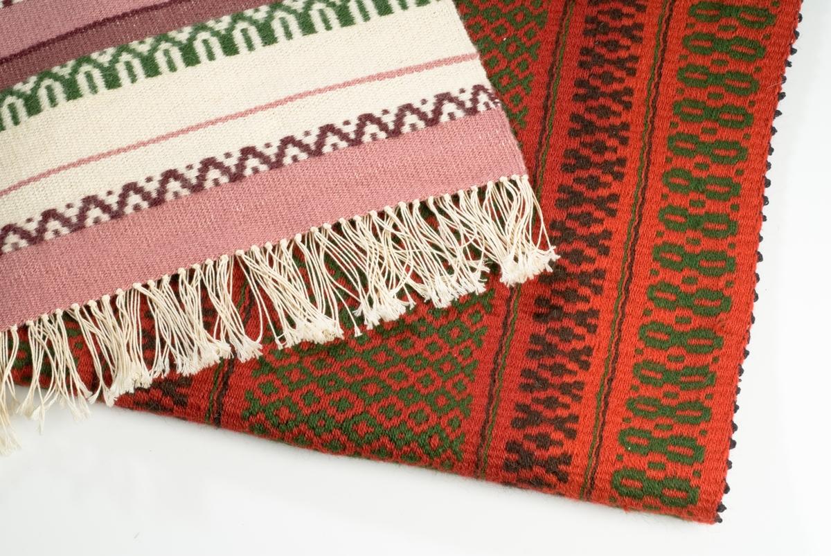 Hjørnet av to vevde tepper. Det ene er rødt med sort mønster. Det andre er med rosa, hvitt og grønt mønster.