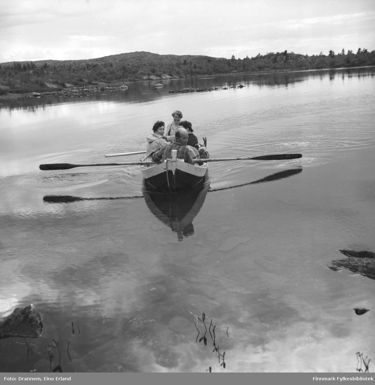 Fire personer sitter i en robåt. Jenny til venstre, Sonja bak og Uuno foran. En ukjent dame ses til høyre i båten.