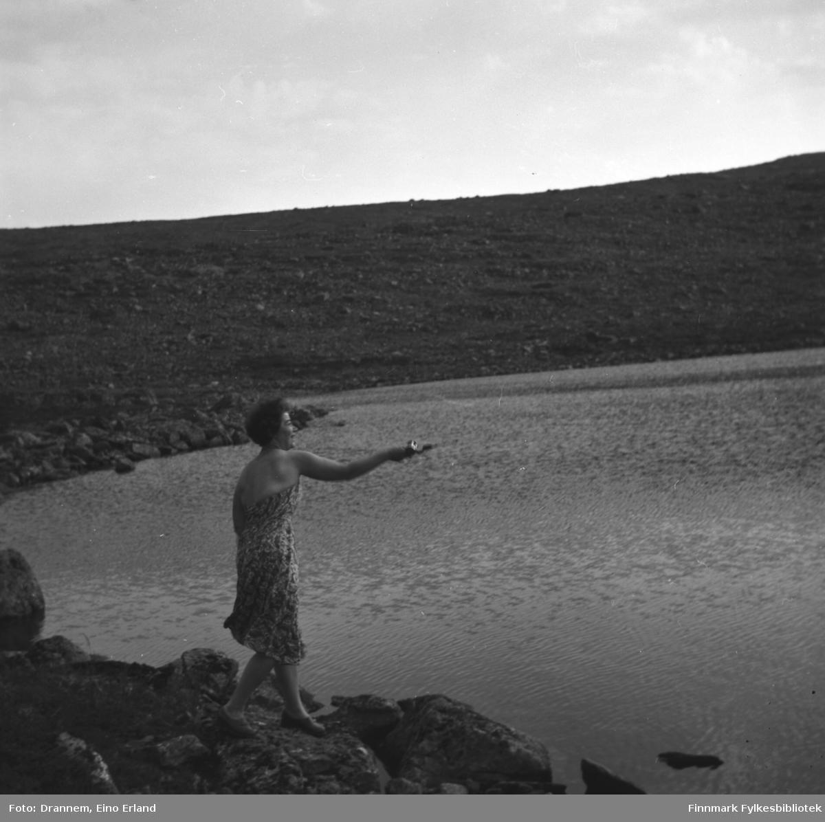 Jenny Drannem fotografert ved bredden av et fjellvann med fiskestang i handa.