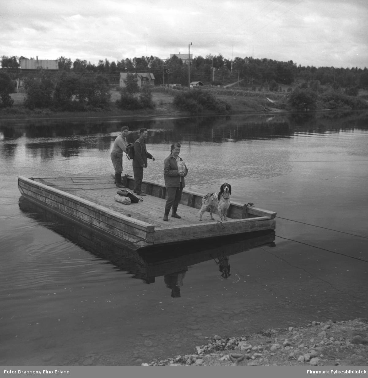 Tre personer og en hund ombord i ferga/prammen over Neidenelva. De er fra venstre: Odd Gabrielsen, Olav Gabrielsen, Turid Lappalainen og hunden Rexi.