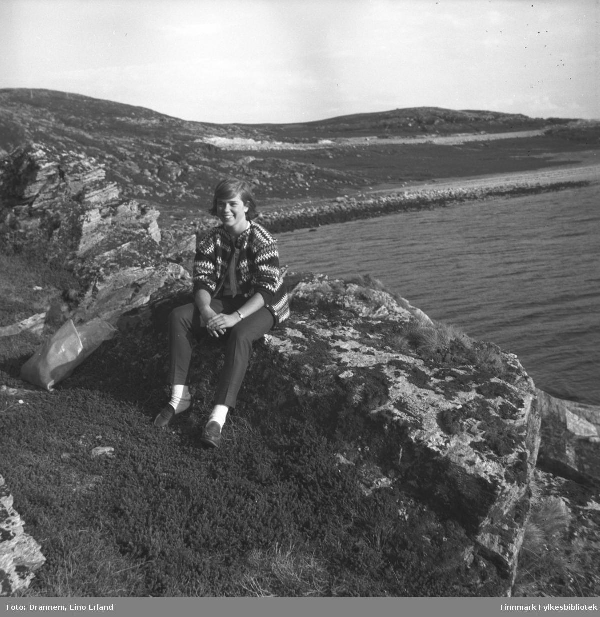 Marit Gabrielsen sitter på en stein i veikanten til Rv94 med Kargenes i bakgrunnen.