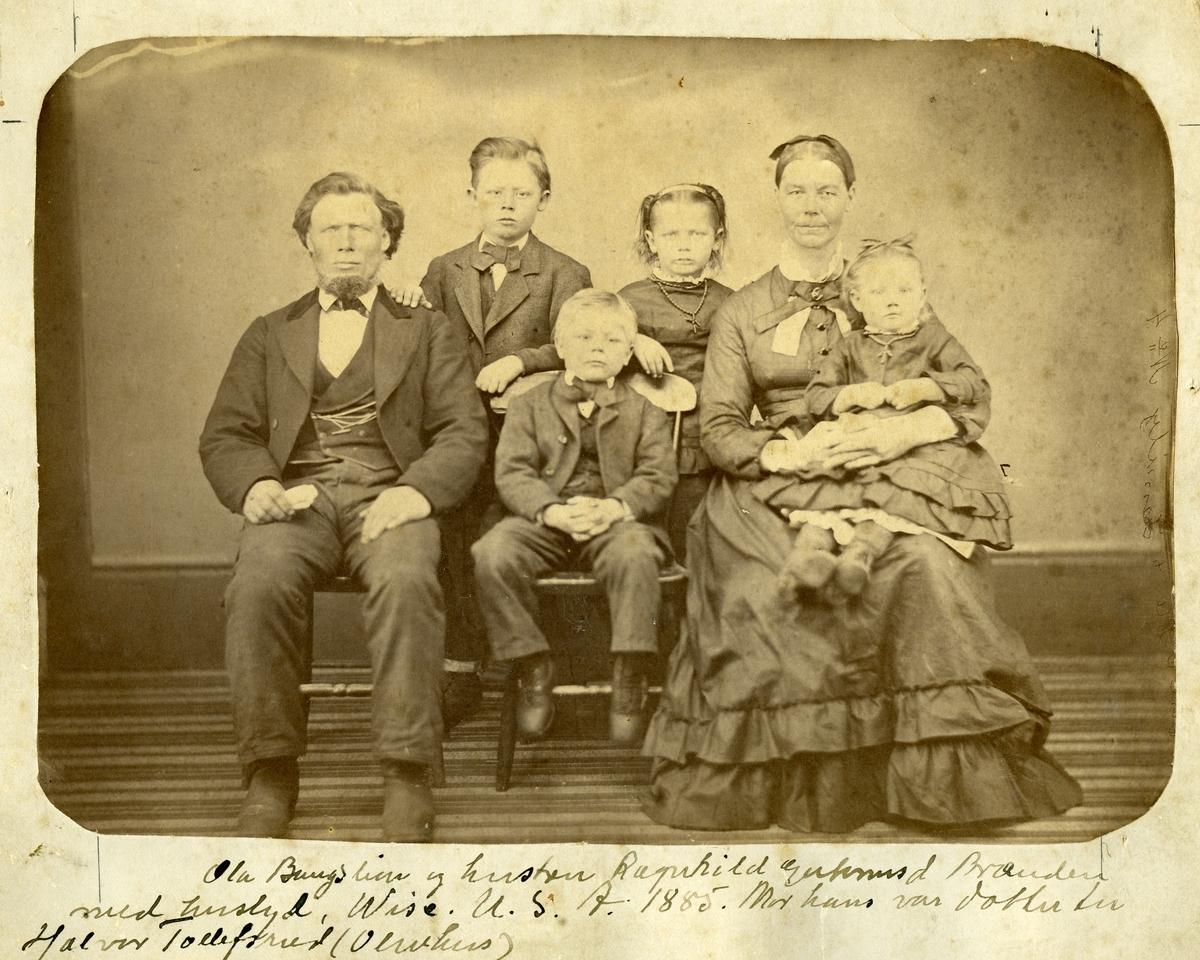 Familieportrett av Ola Bangslien og hustru Ragnhild Brænden og deres fire barn. Bilde er tatt i studio, foran et lerret.