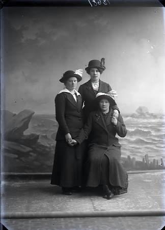 Gruppbild, tre kvinnor i helfigur varav en sitter. samtliga bär hattar. Ateljébild. Beställare: Dalia Johansson.