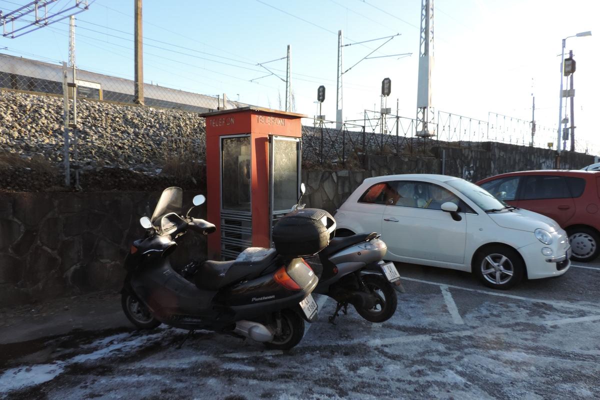 Denne telefonkiosken står ved Sandnes jernbanestasjon, og er blant de 100 vernede røde telefonkioskene i Norge. De røde kioskene ble laget av hovedverkstedet til Telenor (Telegrafverket, Televerket). Målene er så å si uforandret.  Vi har dessverre ikke hatt kapasitet til å gjøre grundige mål av hver enkelt kiosk som er vernet.  Blant annet er vekten og høyden på døra endret fra tegningene til hovedverkstedet fra 1933. Målene fra 1933 var: Høyde 2500 mm + sokkel på ca 70 mm Grunnflate 1000x1000 mm. Vekt 850 kg. Mange av oss har minner knyttet til den lille røde bygningen. Historien om telefonkiosken er på mange måter historien om oss.  Derfor ble 100 av de røde telefonkioskene rundt om i landet vernet i 1997. Dette er en av dem.