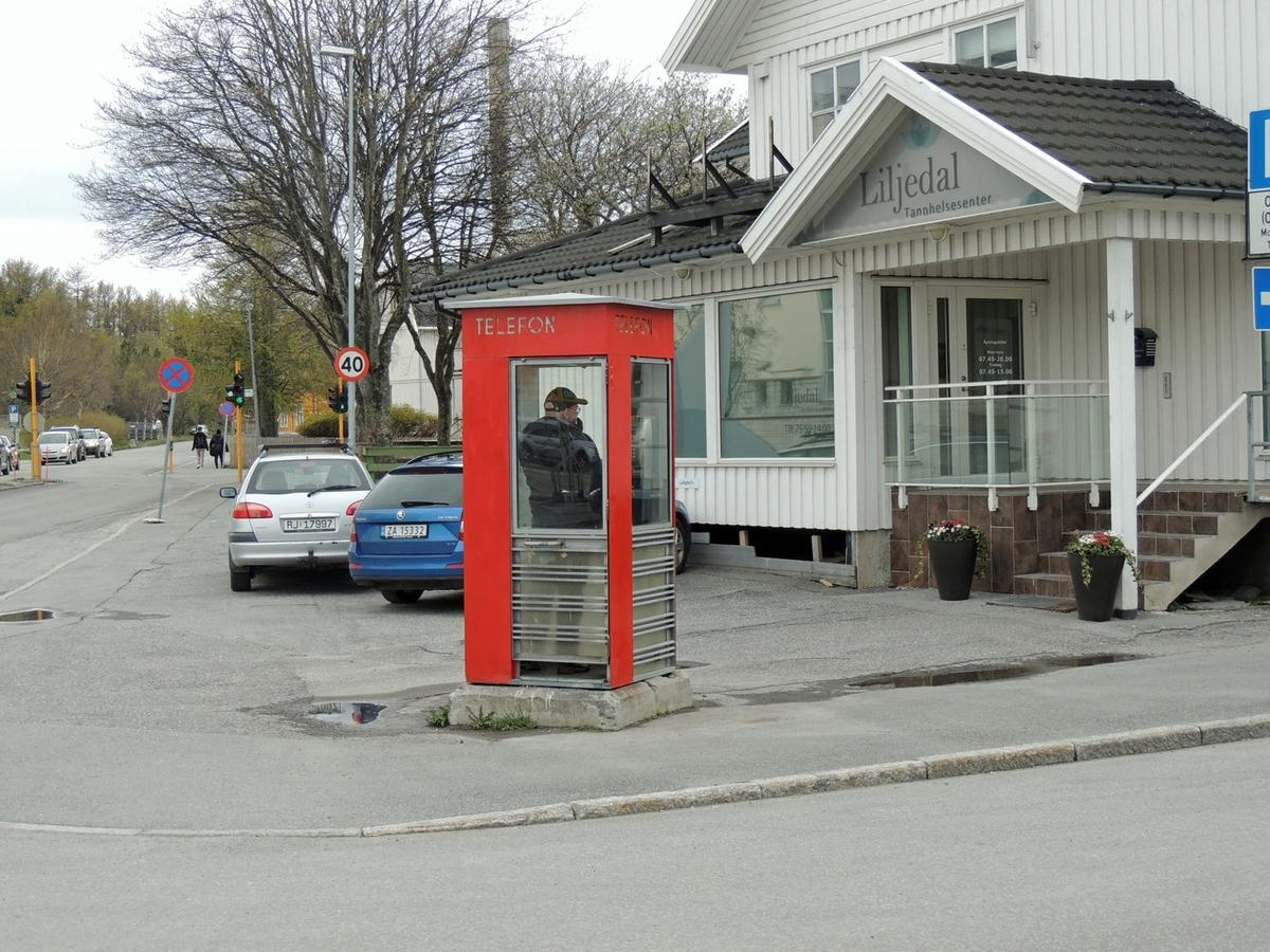 Denne telefonkiosken står ved politihuset i Bodø, og er en av de 100 vernede telefonkioskene i Norge. De røde telefonkioskene ble laget av hovedverkstedet til Telenor (Telegrafverket, Televerket). Målene er så å si uforandret.  Vi har dessverre ikke hatt kapasitet til å gjøre grundige mål av hver enkelt kiosk som er vernet.  Blant annet er vekten og høyden på døra endret fra tegningene til hovedverkstedet fra 1933. Målene fra 1933 var: Høyde 2500 mm + sokkel på ca 70 mm Grunnflate 1000x1000 mm. Vekt 850 kg. Mange av oss har minner knyttet til den lille røde bygningen. Historien om telefonkiosken er på mange måter historien om oss.  Derfor ble 100 av de røde telefonkioskene rundt om i landet vernet i 1997. Dette er en av dem.