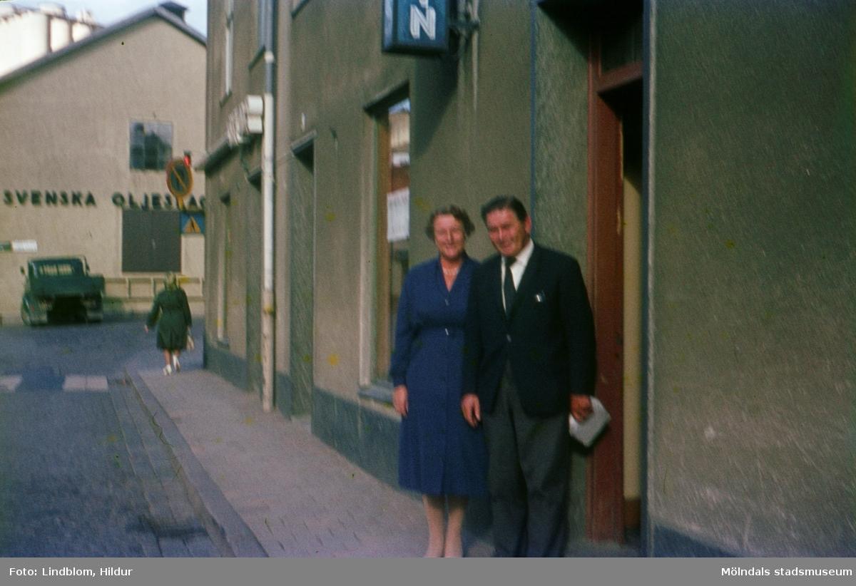 En kvinna och en man står utanför dörren till Josef Anderssons Porslinsaffär med adress Kvarnbygatan 4 vid Gamla Torget i Mölndal, 1960-1970-tal. I samma hus lite längre bort ligger även Rasmussons skoaffär. I bakgrunden ses del av gaveln till huset Kvarnbygatan 6, byggnad tillhörande SOAB.  För mer information om bilden se under tilläggsinformation.