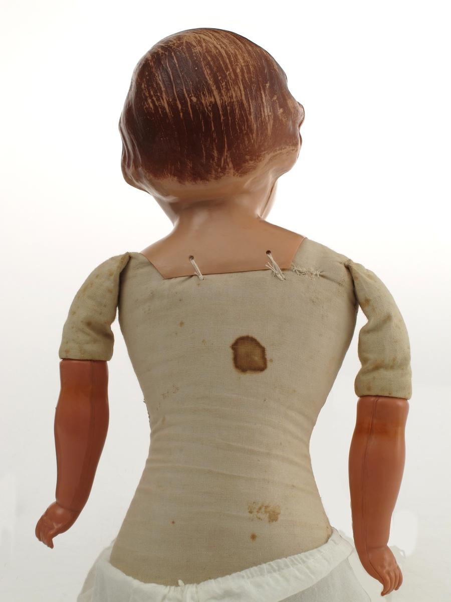 Dukke med dukkeklær. Hode og armer av celluloid, resten av dukken er tekstilt materiale. Kjole bomull, mørk blå farge, borelåslukking. Bukse mammelukker.   Hodet er ikke merket av produsent, men har typisk KaySax-form.