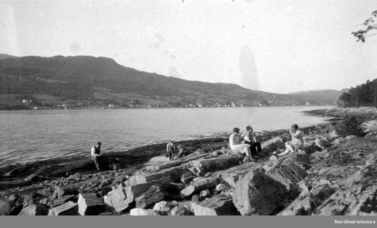 To menn, to kvinner og to barn på en strand i en fjord.Trolig sønner og svigerdøtre, barnebarn av Margrethe og Georg sverdrup.  Fra Nordmøre museums fotosamlinger.