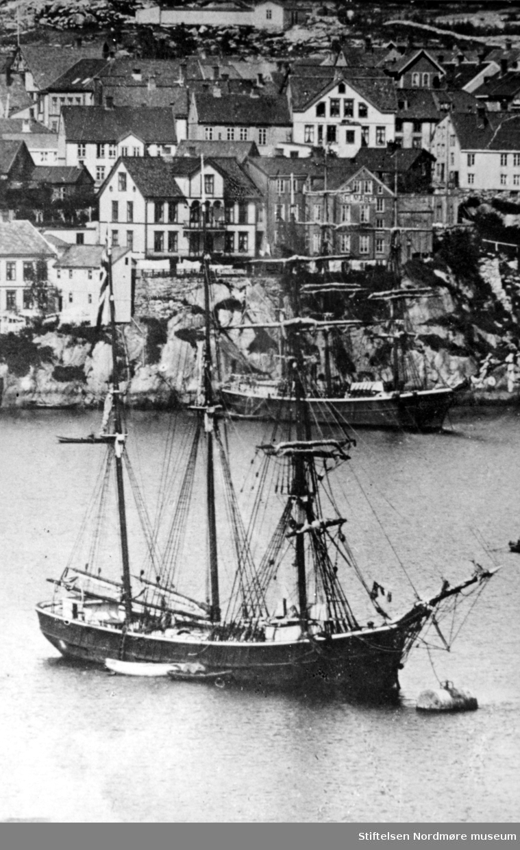 """Bildet viser sansynligvis S/S """" Ina"""" en skonnertbrigg på 252 registertonn fortøyd i """"Storbøya"""" på havna i Kristiansund i 1885. Bildet gir oss en fin oversikt om hvordan havnepartiet fra Kirkeallmenningen til omtrent der hvor Nordmørskafeen er i dag, var på den tiden. Vi ser at skutene ligger akterfortøyd ved Blixhammeren. Navnet på barken som ligger der er ikke kjent. """"Ina""""s redere var N. R. Parelius og Albert Heyerdahl og fører var O. Tomelthy. Skipet ble bygd i Genova i 1874. Kildene forteller at hun var rundgattet og ikke videre pen, men sterk da den var bygd for kisfart. Seilte mest på Amerika og spesielt på Brasil. På Brasilkysten kom den ut for en kastevind som tok hele dokken, riggen og storstangen. Mannskapet fikk rigget nødrigg, og etter to uker greide de å komme seg tilbake til avseilingshavnen, som var Bahia.  Her ble de liggende i fire måneder for reparasjon. Deretter gikk turen til London, hvor hun ankom den 15/7-1886. På den påfølgende turen over Atlanteren, under meget vanskelige og farlige forhold, berget de 10 mann fra en bark fra Rostock. Redningen ble utført av styrmann Alnæs sammen med tre matroser. Barken sank tre timer etter at man hadde fått de skipbrudne ombord i S/S """"Ina"""". Skuta seilte inn til Falmouth med de overlevende.  Korte glimt av """"Ina""""s seilingsliste viser at hun ankom Arkhangelsk den 24/7-1885 og gikk derfra den 12/8 til Davenport. Fra Trinidad gikk hun den 8/2-1887 til Falmouth. Kapteinen var O. Tomelthy. Det fremgår, som kildene sier, at hun var noe rundgattet, men man har vanskelig med å si seg enig i at hun ikke var pen. S/S """" Ina"""" ble i 1887 solgt til Porsgrunn.                                                                            Kilde : Kristiansund på de 7 hav av Kjell Dønheim.                                                                                 Se FAKf-100296.187121    (KMb-1987-005.3854)                                                                           Se FAKf-100296.187127    (KMb-1987-005.3860)   """