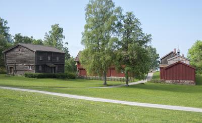 En grå tømmerbygningn i to etasjer står til venstre i bildet, midt på ser vi to bjørker og til høyre en rød, plankebeslått bygning.