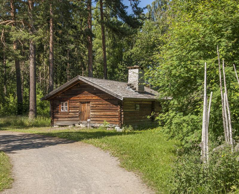 Brunt tømmerhus med flistak og høy pipe ligger idyllisk langs en grusveg med en skigard til høyre og høyre furuer bak.