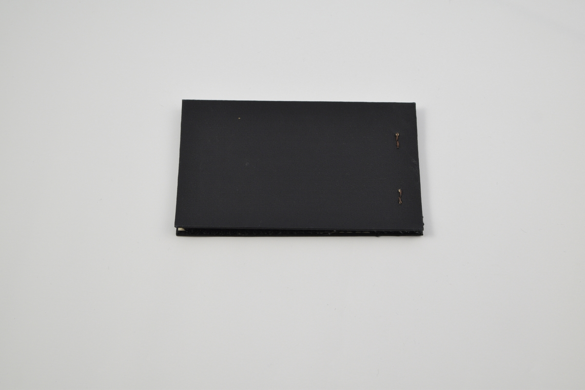 Prøvebok med 5 prøver. Tynne ullstoffer uten eller med diskret mønster. Alle stoffer er merket med en rund papirlapp festet med metallstifter hvor nummer er påskrevet for hånd.  Stoff nr. 766 (grå), 812 (grå), 900 (grå/sort), 953 (grå), 835 (sort).