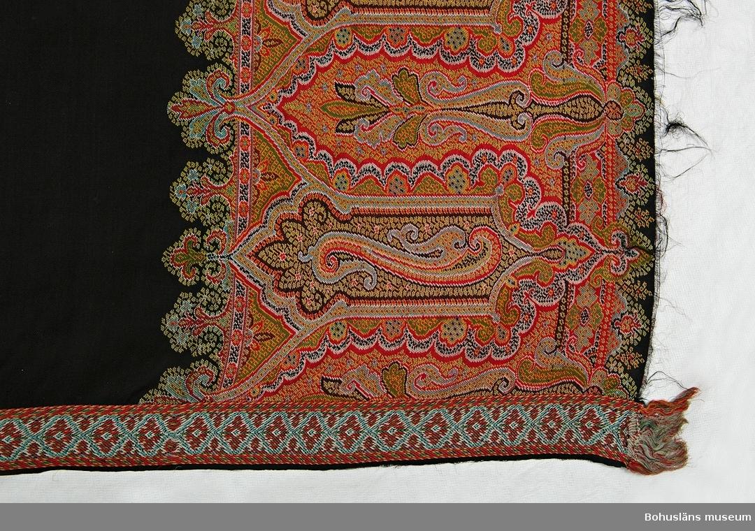 Rektangulär schal med svart bottenfärg. Längs kortsidorna ca 35 cm breda bårder med ett detaljerat orientalisk-inspirerat mönster i rött, gult, vitt, ljusblått, ljusgrönt och svart. Varpen är rödfärgad vid de breda bårderna. Längs långsidorna smala bårder, ca 4,5 cm breda, vävda i annan bindning än resten av schalen. På grund av det komplicerade mönstret kan man med säkerhet säga att schalen är vävd i jacquardvävstol. Schalar av det här formatet började vävas på 1840-talet i samband med att krinolinen kom. De viktes dubbla vid användning. Schalar av Paisleytyp miste sin populäritet på 1870-talet, sista schalen vävdes i Paisley 1886. Dateringen gjord utifrån dessa uppgifter.  Några mycket små hål och lagningar. På väg att uppstå bristning på mitten där schalen varit vikt. Fåtal fläckar eller blekmärken. Sliten längs kortsidorna, fransarna till stora delar bortslitna.