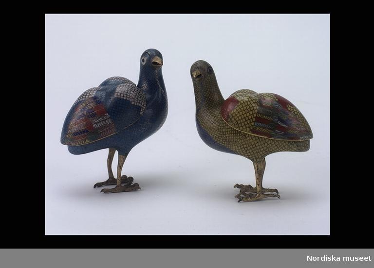 """Huvudliggaren: """"Rökelsekar, 2 st, koppar, förgylld cloisonné. En gul, en röd fågel. Fjädrar polykroma. Rygg som lock. Ca 1900."""""""