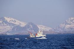 Fiskebåt på havet, Lofoten, med Lofotveggen i bakgrunnen