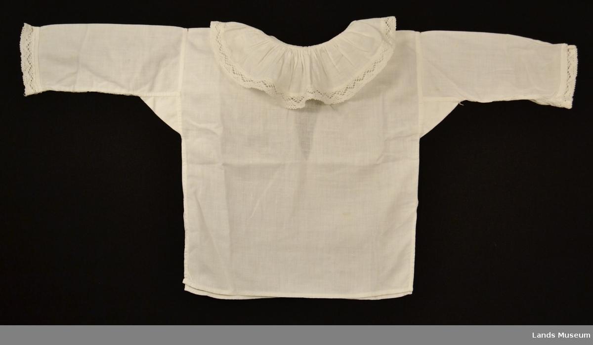 Babyskjorte med isydderme og kile. Splitt bak med knyttebånd. Krage og ermer kantet med knipleblonde.