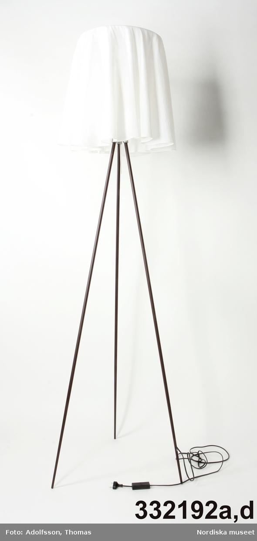 """Golvlampa för elektrisk belysning stående på tre ben av rödbrun metall. Upptill konformad plasttratt omslutande bred lampsockel. Trattens lock en rund lösttagbar platta av plexiglas. Tre tunna metallstag fästa i plattans ytterkanter, vidgas utåt och är bärare av  rund ring i klar plast. Plastknoppar längs innerkanten av ringen utgör fästen för vit textilkjol. På kjolen diskret text i vitbroderi: """"Starck"""". Svart sladd avslutad med stickkontakt.  Plattan av plexiglas nytillverkad ersättning för sönderbränt, kasserat rasterlock av plast. Plasttratten något missfärgad av för hög värme. Glödlampa saknas. (Det ursprungliga rasterlocket finns kvar på den andra lampan i paret, dock brännskadat). /Maria Maxén 2016-02-29"""