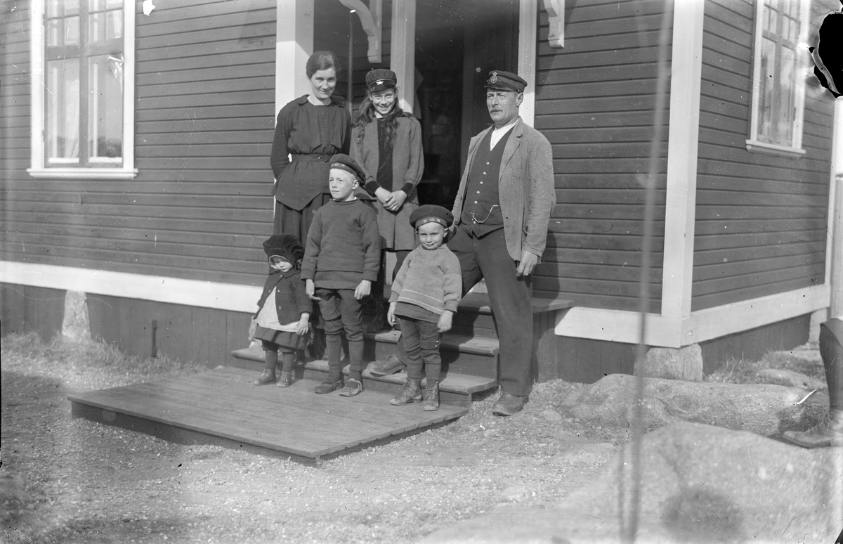 Familjen på trappan till huset