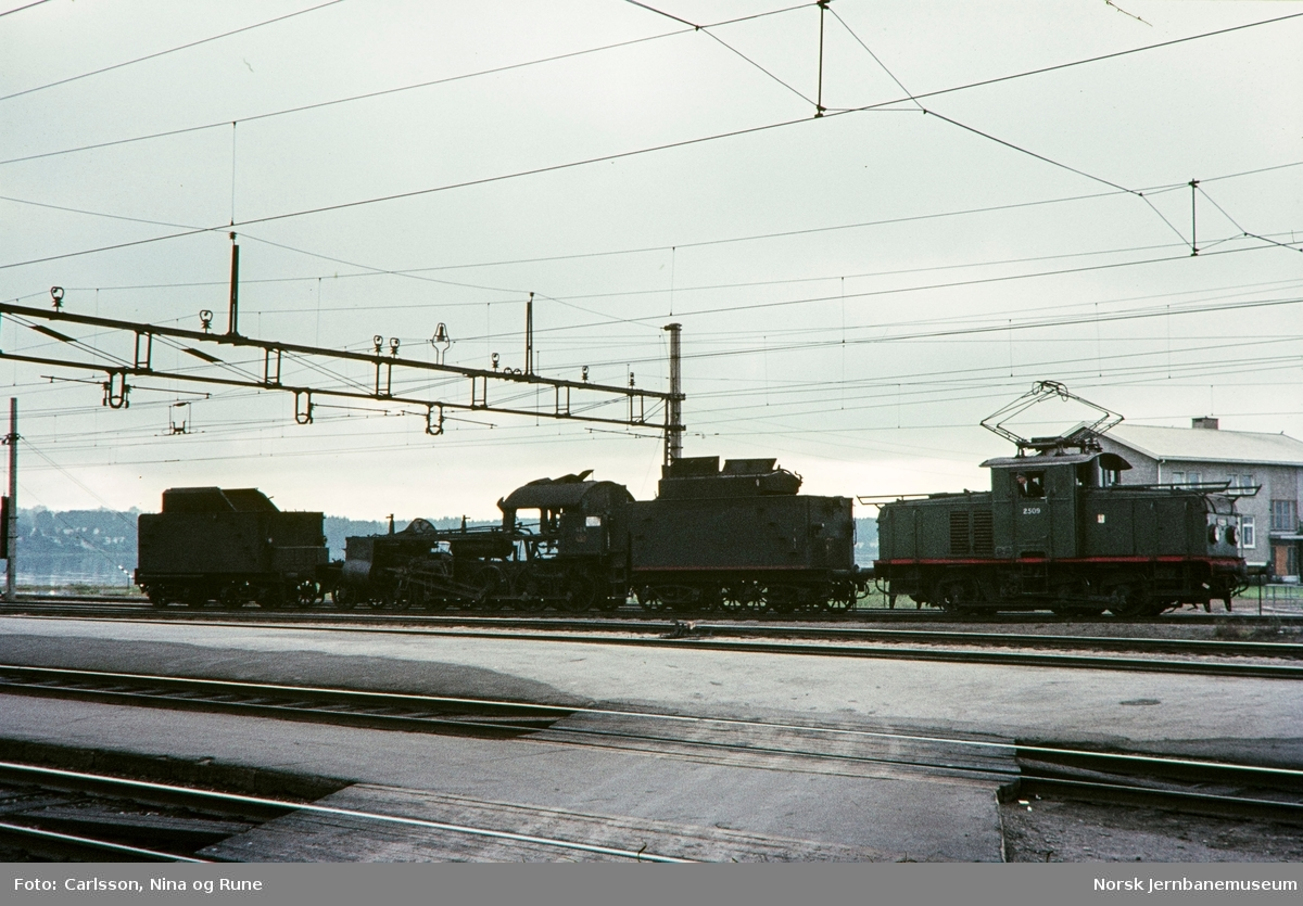 Elektrisk skiftelokomotiv El 10 2509 med utrangert damplokomotiv på Hamar stasjon