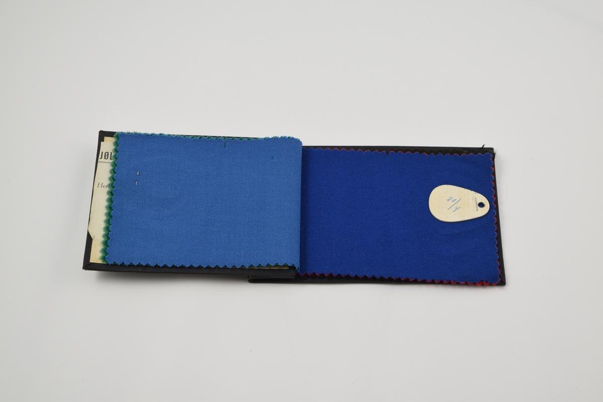 """Prøvebok med 8 prøver. Tynne ensfargede stoff, toskaftvev.  Alle stoffer er merket med en dråpeformet tynn trefiner plate festet med metallstifter hvor nummer er påskrevet for hånd. På baksiden av merkelappene er det limt en papirlapp hvor det er trykket """"NORSK FABRIKAT"""".   Stoff nr. 80/1 (lys grønn), 80/2 (mørkere grønn), 80/3 (blå) 80/4 (mørkere blå), 80/5 (rød), 80/6 (brun), 80/7 (mørk blå). 80/8 (sort)."""