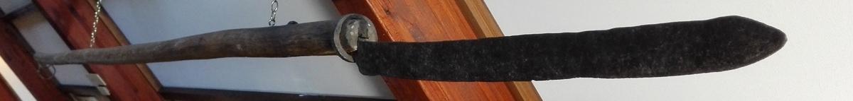 1 brugdekniv.  Konf.no.3180. Den sverdlignende eneggete i odden tveegget kniv er 68 cm lang med en 26 cm lang tange, der er indfeldt i et træskaft. Tangens ende er vinkelbøiet og drevet gjennem skaftet, paa hvis ende en jernring, der fastholder tangens anden ende. Træskaftet rundt, diameter ca. 6 cm, av furu og 307 cm langt. Gave fra gaardbruker J.K.Laagø, Sulen.